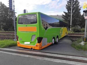 Řidič autobusu se chtěl vyhnout komplikacím na dálnici, tak z ní sjel. Uvízl ale na přejezdu